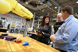Gateway Automated Manufacturing instructor JD Jones demonstrates robotics equipment to Lt. Gov. Rebecca Kleefisch