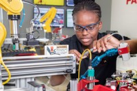Student Janell McFarland working with advanced manufacturing equipment
