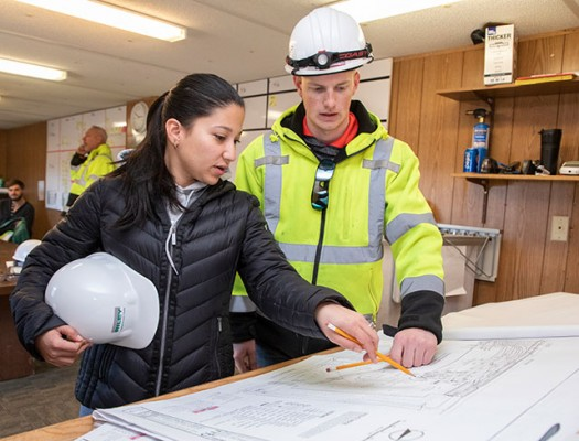 Construction students looking at blueprints