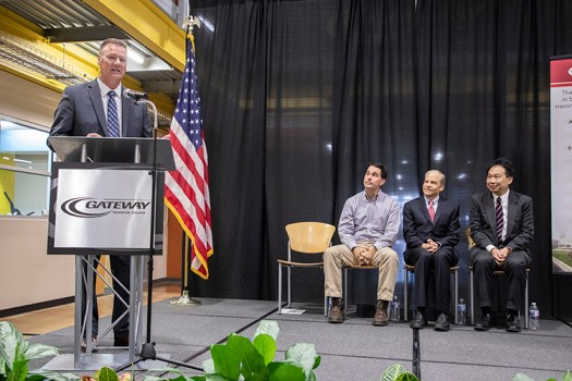 Gateway Technical College President and CEO Bryan Albrecht is speaking at the podium during the SC Johnson iMET Center expansion and renovation groundbreaking event Oct. 22. Seated (l-r): Governor Scott Walker; Fisk Johnson, SC Johnson chairman and CEO; Alan Yeung, Foxconn director of US Strategic Initiatives.